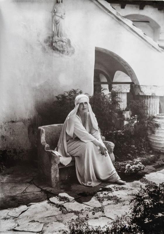 Regina Maria pe o bancă de piatră în curtea Castelului Bran <br />  Sursă foto: Arhivele Naționale ale României