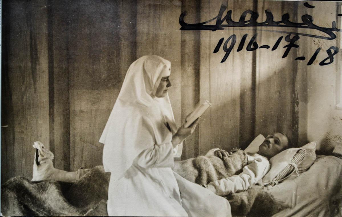 Regina Maria citind unui rănit, pe patul de spital din Coțofenești, noiembrie 1917 <br /> Sursă foto: Arhivele Naționale ale României