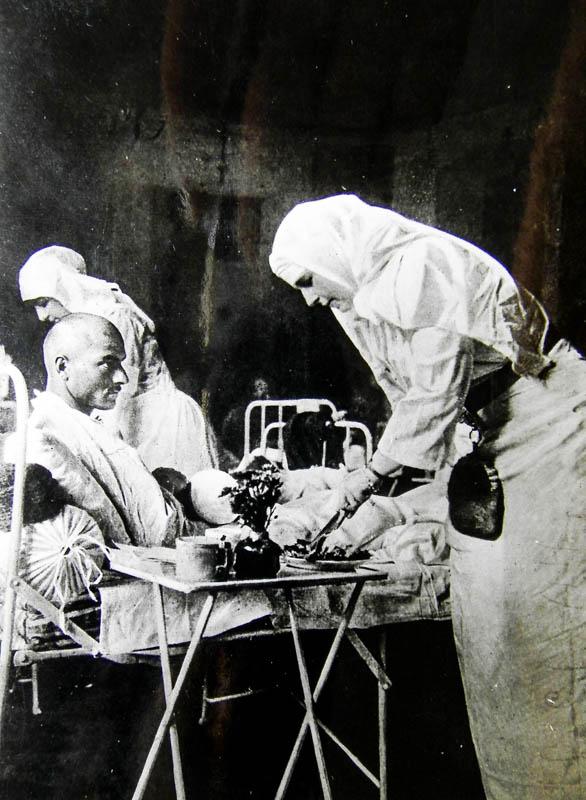 Regina Maria la căpătâiul unui rănit în 1917 <br /> Sursă foto: Arhivele Naționale ale României