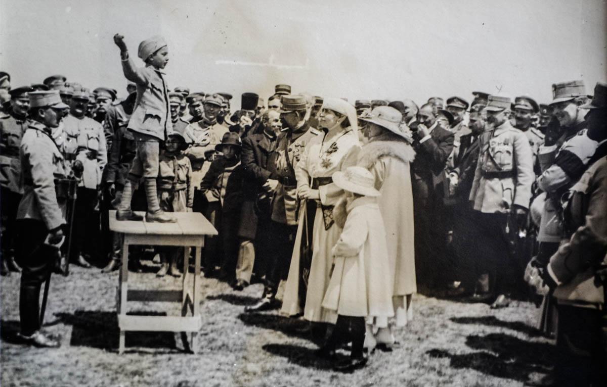 Regina Maria ascultând o poezie recitată de un copil de trupă la încheierea unei parade lângă Iași, în vara anului <br /> Sursă foto: Arhivele Naționale ale României 1917