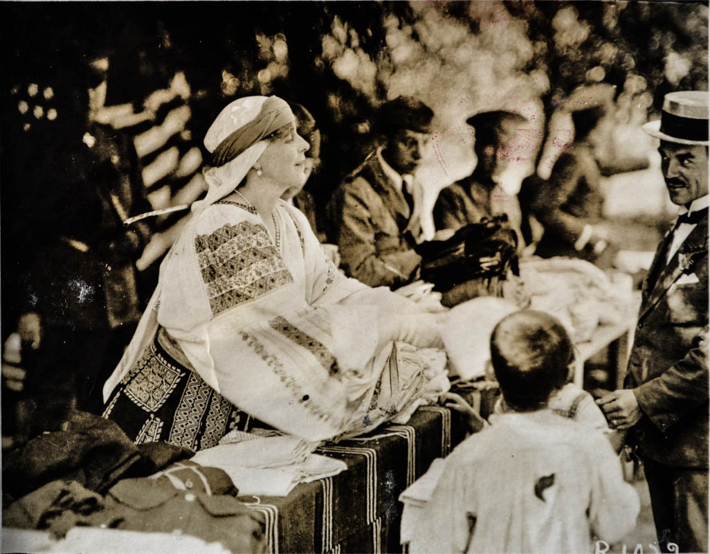 Misiunea Crucii Roșii Americane în România. Regina Maria îmbrăcată în costum național, oferind mâncare și ajutor copiilor săraci și orfani, afectați de război  <br /> Sursă foto: Arhivele Naționale ale României