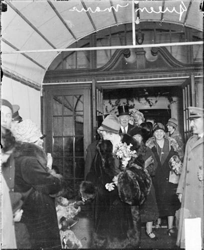 Regina Maria în Chicago, ținând în mână un buchet de flori, la ieșirea din clădire <br /> Sursă foto: https://explore.chicagocollections.org/
